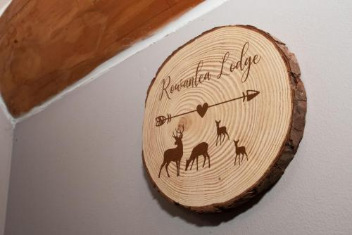 Close up of log with rowanlea lodge on it.